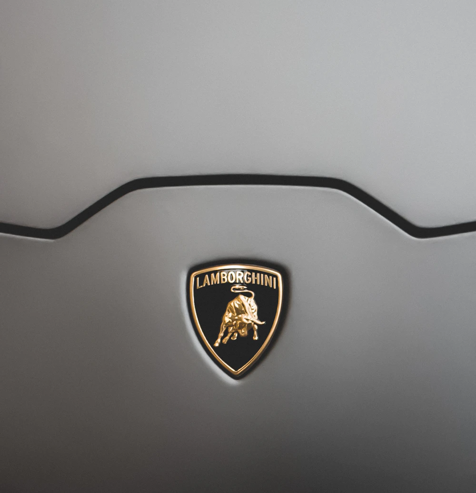 The Lamborghini logo is looking like a shield that is loaded up with a dark foundation and delineated with gold. Across the highest point of the shield is the word Lamborghini in capital letters over a picture of a brilliant bull.
